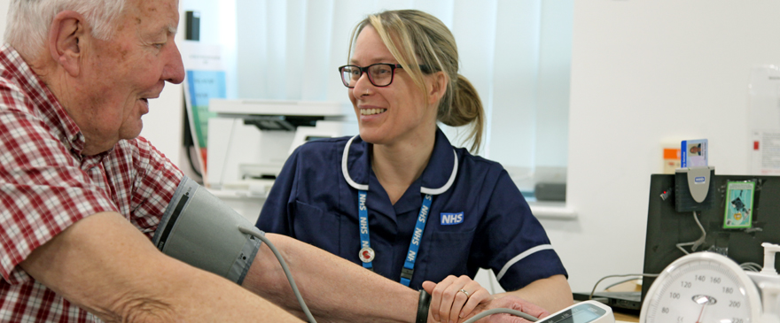 Nurse taking a blood pressure reading from a male service user.