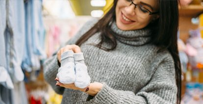 Lady holding baby socks in her and and smiling.